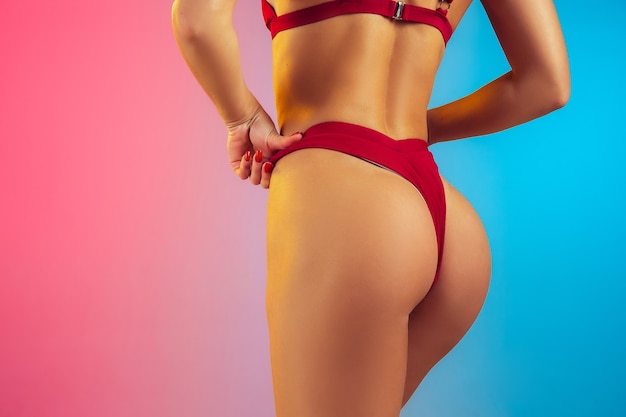 Primo piano di una giovane donna sportiva e in forma in un elegante costume da bagno rosso su una parete sfumata, un corpo perfetto pronto per l'estate