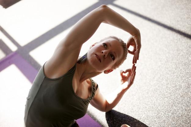 Chiuda in su di una ragazza che fa una danza mentre esegue un asana di yoga