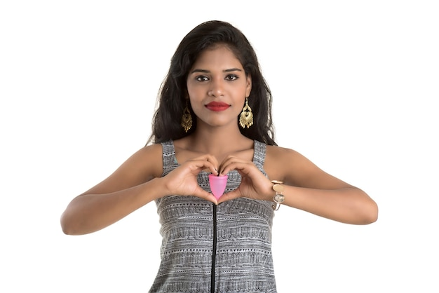 Close-up di giovane ragazza mani tenendo la coppetta mestruale, concetto di ginecologia, mostrando pollice in alto approvando l'uso della coppetta mestruale