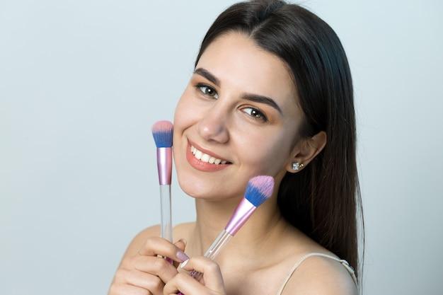 Primo piano di una giovane ragazza in un top leggero su uno sfondo bianco che fa un trucco facciale. una bella donna tiene un pennello cosmetico vicino al viso e sorride.