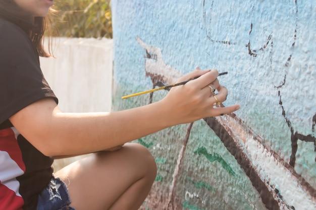 Primo piano di una giovane ragazza che dipinge un muro con un pennello in strada.