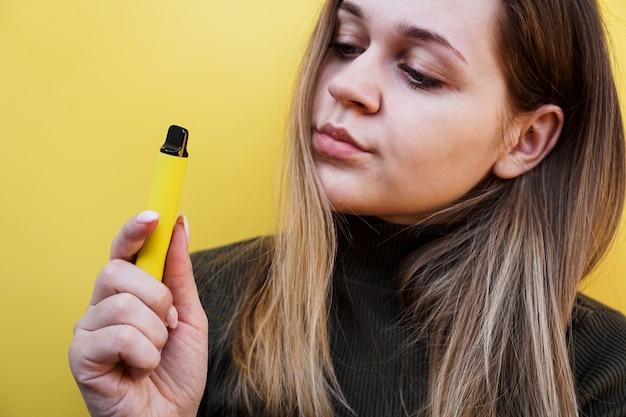 Primo piano di una giovane ragazza che fuma una sigaretta elettronica usa e getta. sfondo giallo brillante. alternativa alle sigarette normali e allo svapo