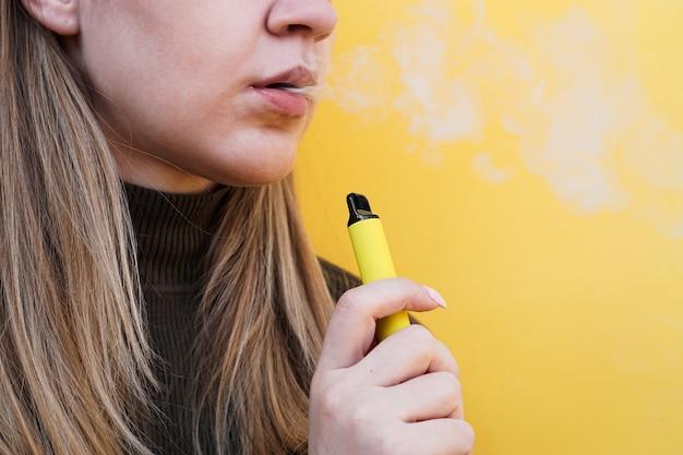 Primo piano di una giovane ragazza che fuma una sigaretta elettronica usa e getta ed espira fumo. sfondo giallo brillante. alternativa alle sigarette normali e allo svapo