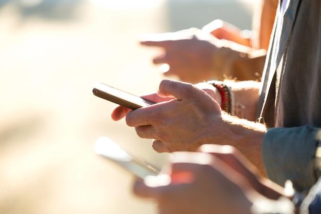 Primo piano di un giovane gruppo di amici che chiacchierano con i loro smartphone in strada.