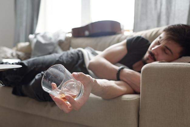 Primo piano di giovane ragazzo che dorme con un bicchiere di whisky vuoto sul divano dopo la festa a casa