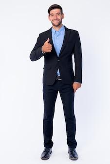 Chiuda in su di giovane uomo d'affari persiano barbuto bello in vestito isolato