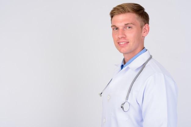 Chiuda in su del medico del giovane uomo bello con capelli biondi isolati