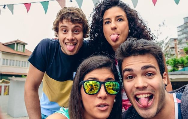 Primo piano di giovani felici che cercano e tirano fuori le lingue divertenti in una festa estiva all'aperto. concetto di stile di vita dei giovani.