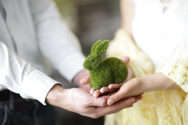 Close up.giovane coppia amorosa che tiene un coniglio giocattolo verde.