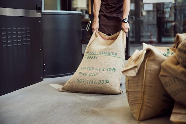 Primo piano di un giovane uomo in grembiule che trasporta un sacco di tela con chicchi di caffè arabica
