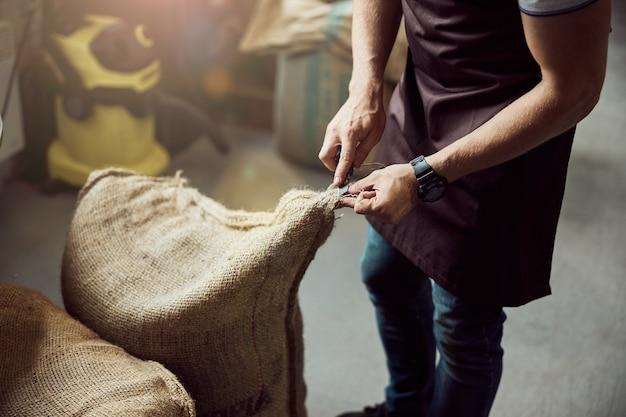 Primo piano di un giovane in grembiule che taglia una borsa aperta con chicchi di caffè tostati in deposito