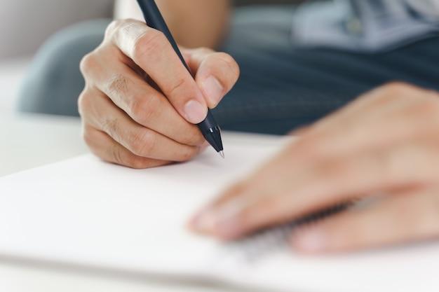 Primo piano di un giovane con mani di stoffa casual che scrivono sul blocco note, taccuino con penna a sfera sul tavolo.