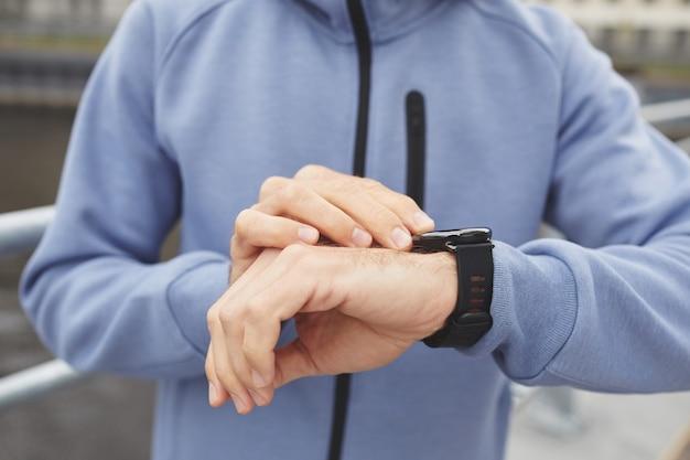 Primo piano del giovane controllando il suo polso sul braccialetto fitness durante il suo jogging all'aperto