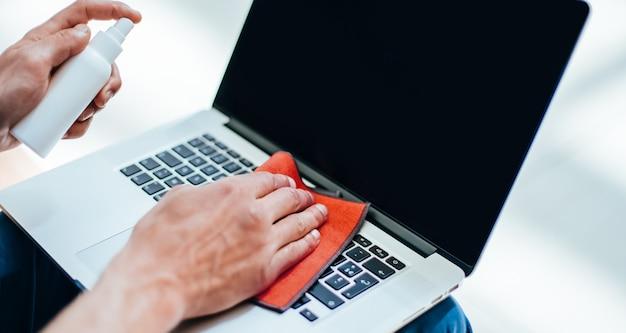 Avvicinamento. giovane che decontamina il suo laptop. concetto di tutela della salute