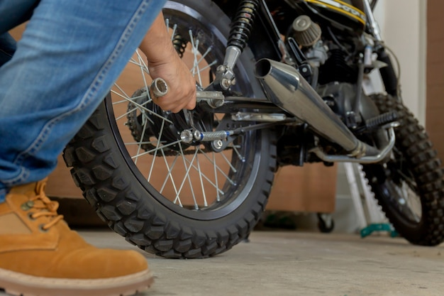 Primo piano del motociclo della riparazione della mano del giovane, del hobby meccanico e del concetto di riparazioni.