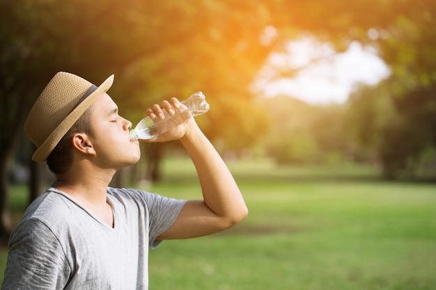 Chiuda sulla mano del giovane che tiene la bottiglia di acqua potabile fresca fresca da una plastica.