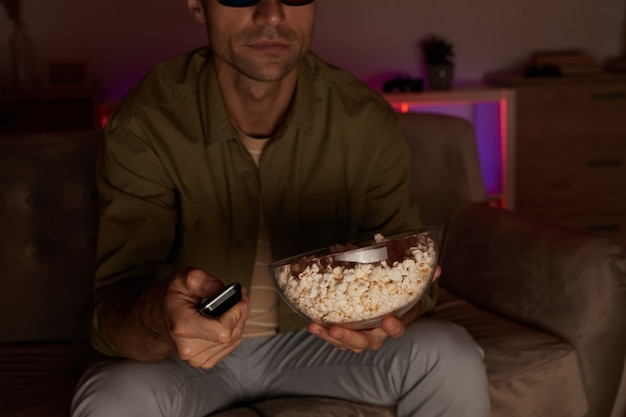 Primo piano di giovane che tiene ciotola con popcorn e telecomando e guardare la tv sul divano di casa
