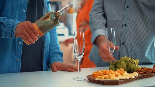 Chiuda in su del giovane che versa vino bianco nei bicchieri. due generazioni gustano una coppa di champagne nell'accogliente sala da pranzo mentre le donne preparano la cena salutare