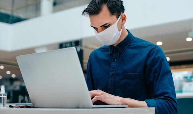Avvicinamento. giovane uomo in una maschera protettiva seduto davanti a un computer portatile aperto. foto con copia-spazio