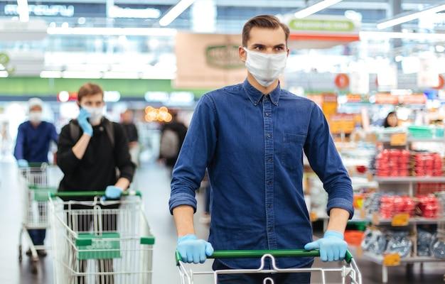 Avvicinamento. giovane uomo in una maschera protettiva con un carrello della spesa