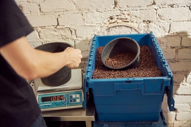 Primo piano di un giovane che mette il secchio sulla bilancia mentre si trova vicino a un contenitore di plastica con chicchi di caffè