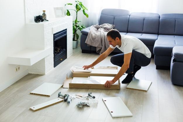 Primo piano di un giovane che mette mobili da assemblare mentre si trasferiscono nella tua nuova casa.
