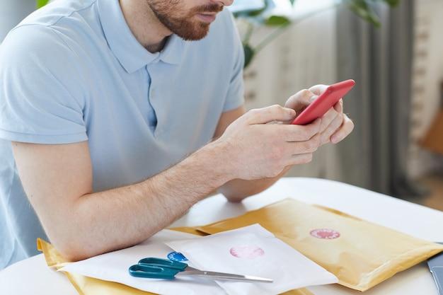 Primo piano di giovane uomo seduto al tavolo e utilizzando il suo telefono cellulare durante l'apertura delle lettere a casa