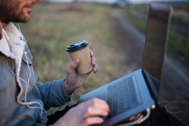 Primo piano di giovane uomo seduto con il computer portatile su gambe e tazza di caffè in mano