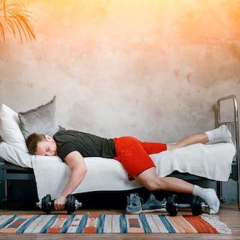 Primo piano di un giovane in uniforme sportiva sta riposando, dormendo su un letto con un manubrio. saloni atleta e posticipa l'allenamento