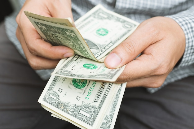 Primo piano giovane in piedi mano tenere contare la diffusione del denaro in contanti.