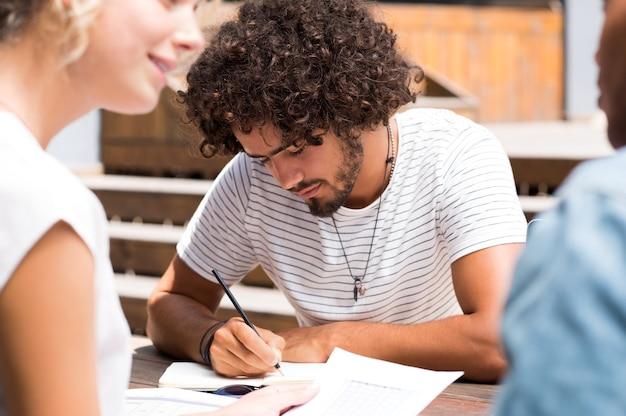 Primo piano di un giovane che studia con gli amici