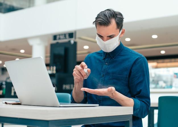 Avvicinamento. giovane uomo utilizzando antisettico durante il lavoro. foto con copia-spazio