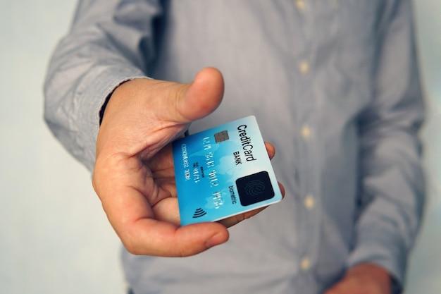 Primo piano di un giovane che utilizza la carta biometrica delle impronte digitali per effettuare il pagamento online senza un codice pin. l'uomo d'affari paga con carta di credito con scanner biometrico. semplice tocco del dito per eseguire la transazione.