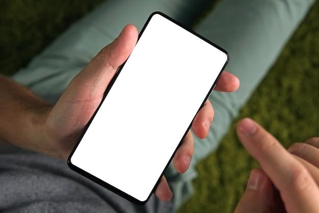 Primo piano di un giovane che utilizza lo smartphone con lo schermo bianco. la persona è in linea da uno smartphone. l'uomo tiene un telefono e alza il dito indice destro per toccare lo schermo. montaggio schermo vuoto