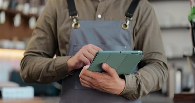 Primo piano della cameriera del giovane che utilizza la tavoletta digitale al bancone e prende gli ordini dai clienti nella caffetteria.