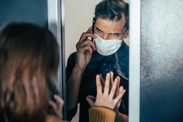 Avvicinamento. un giovane e una donna si guardano ansiosamente attraverso il vetro. foto con copia-spazio
