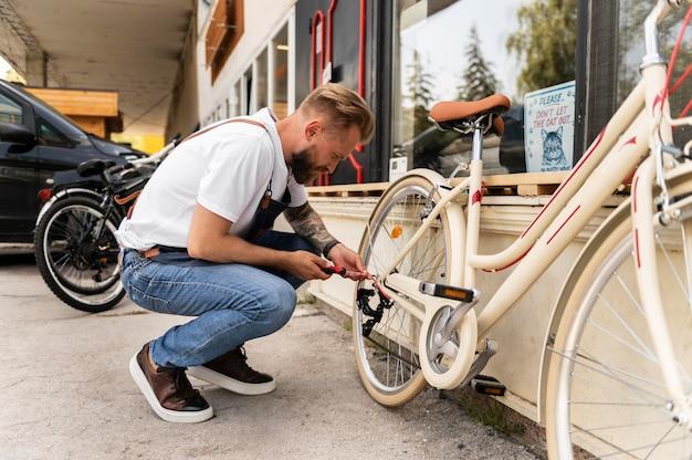 Primo piano su un giovane che lavora su una bicicletta