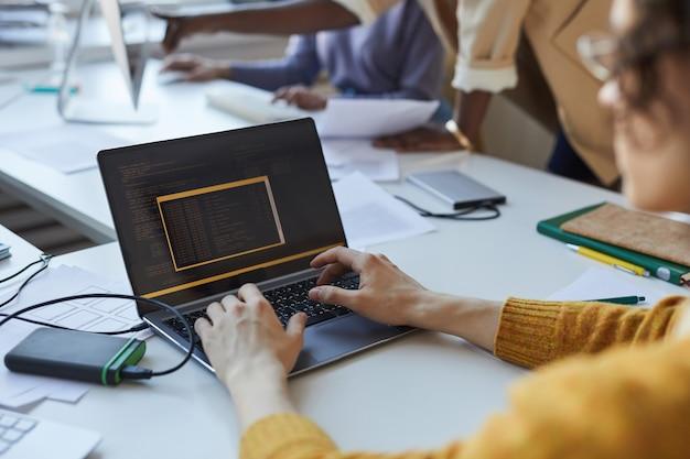 Primo piano di un giovane che scrive codice durante l'utilizzo del laptop in ufficio con un team di sviluppatori di software, spazio di copia