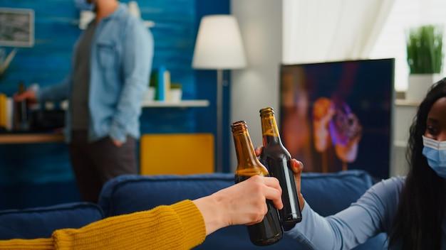 Primo piano delle mani dei giovani che tostano e rallegrano una bottiglia di birra che trascorrono il tempo libero in soggiorno rispettando la distanza sociale per prevenire la diffusione del virus. diverse persone che si godono la festa nell'epidemia