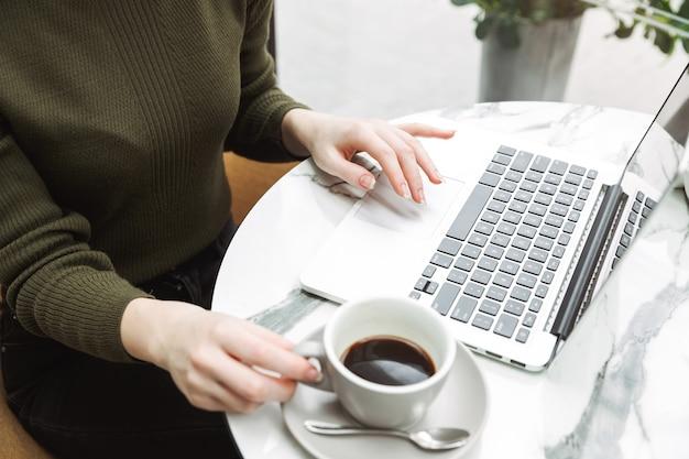 Primo piano di una giovane donna dai capelli rossi che si rilassa al tavolino del bar all'interno, beve caffè, lavora al computer portatile