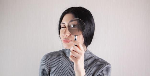 Chiuda in su di giovane donna castana seria che osserva tramite la lente d'ingrandimento