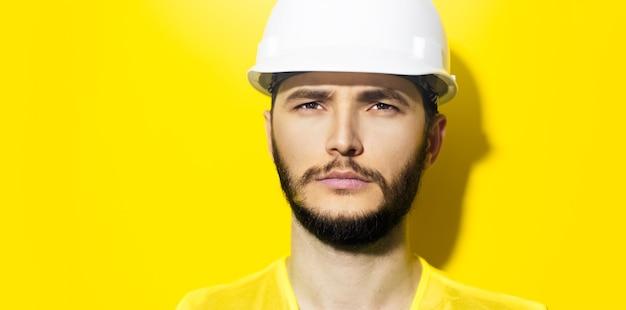 Primo piano giovane uomo serio architetto, ingegnere costruttore, indossando il casco di sicurezza da costruzione bianco e giacca gialla isolato sul muro giallo.