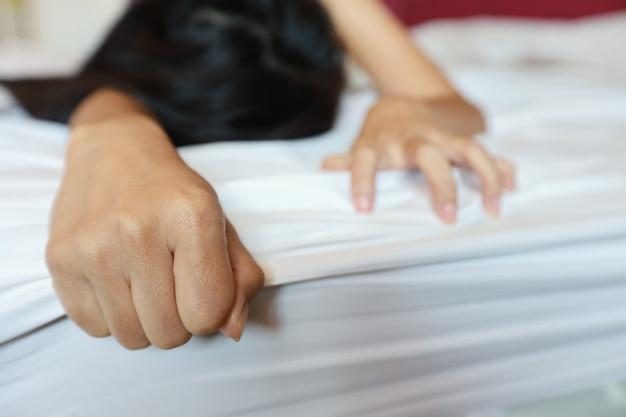 Chiuda in sulla mano di giovane donna sexy tirando lenzuola bianche in estasi in hotel