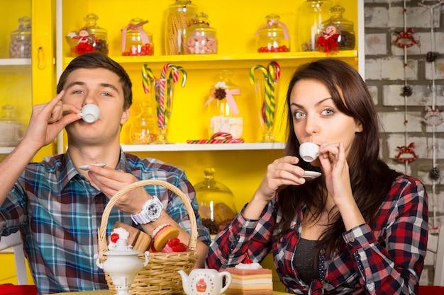 Chiuda in su giovane coppia bianca in abiti casual facendo sorseggiando un drink posa da piccole tazze bianche mentre si guarda la telecamera. catturato al cafe