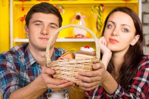 Chiuda in su giovane coppia bianca in camicie a scacchi offrendo cesto di pasticceria mentre si guarda la telecamera.