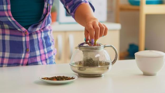 Primo piano di una giovane donna che aggiunge acqua calda su foglie di tè a base di erbe. casalinga che prepara il tè verde per la colazione usando la teiera in una cucina moderna seduta vicino al tavolo con il bollitore in attesa di infondere.