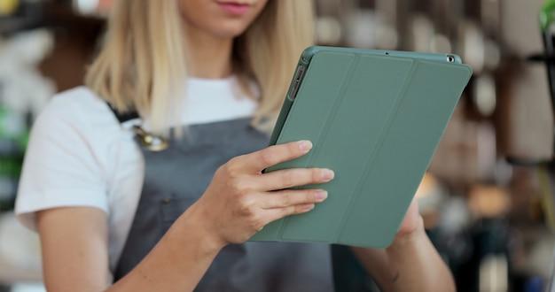 Primo piano di una giovane barista che utilizza la tavoletta digitale al bancone e prende gli ordini dai clienti nella caffetteria.