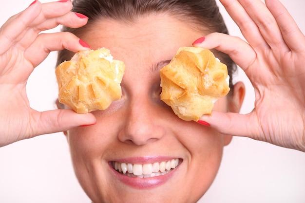 Un primo piano di una giovane donna che si copre gli occhi con bignè alla crema su bianco