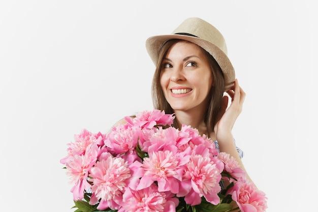 Primo piano di una giovane donna in abito, cappello che tiene il mazzo di bellissimi fiori di peonie rosa isolati su sfondo bianco. san valentino, concetto di vacanza per la giornata internazionale della donna. zona pubblicità.