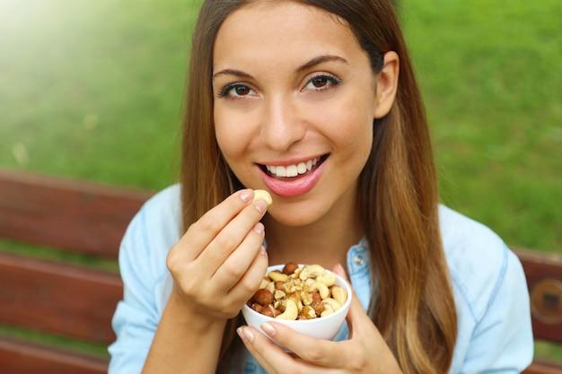 Primo piano di giovane donna che mangia noci miste nel parco.